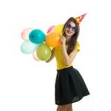 Jeune fille drôle dans des vêtements lumineux tenant beaucoup de ballons et sourire Photographie stock libre de droits