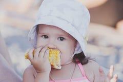 Jeune fille drôle mangeant d'un maïs bouilli photo stock