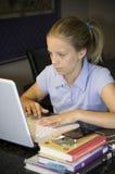 Jeune fille effectuant à la maison le travail Images libres de droits