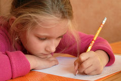 Jeune fille effectuant le travail d'école photographie stock