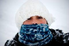 Jeune fille empaquetée vers le haut de l'extérieur dans la neige. Photo libre de droits