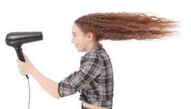 Jeune fille employant le hairdryer Images stock