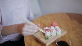 Jeune fille en gros plan mangeant des sushi avec des baguettes dans un restaurant japonais banque de vidéos