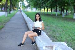 Jeune fille en parc apprenant avec le comprimé image stock