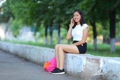 Jeune fille en parc apprenant avec le comprimé photos stock