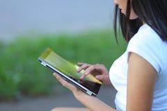 Jeune fille en parc apprenant avec le comprimé images stock