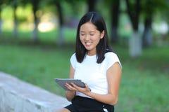 Jeune fille en parc apprenant avec le comprimé image libre de droits
