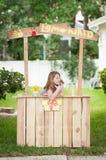 Jeune fille ennuyée sans des clients à son stand de limonade Photographie stock libre de droits