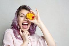Jeune fille enthousiaste avec les cheveux pourpres couvrant son oeil par le dessert doux de fruits L'espace pour le texte image libre de droits