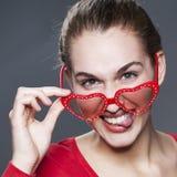 Jeune fille espiègle avec les verres rouges pour l'amour d'amusement Photographie stock