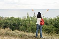 Jeune fille et x28 ; brunette& x29 ; et jeans avec un sac à dos rouge regardant  Photographie stock libre de droits