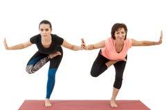 Jeune fille et femme mûre faisant le yoga photos libres de droits