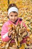 Jeune fille et les feuilles d'automne Photographie stock