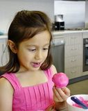 Jeune fille et petit gâteau. Photographie stock libre de droits