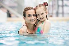 Jeune fille et sa mère étreignant dans la piscine photos libres de droits