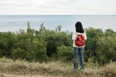 Jeune fille et x28 ; brunette& x29 ; et jeans avec un sac à dos rouge regardant  Images stock
