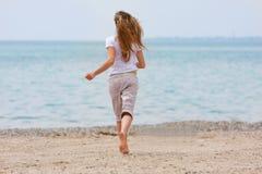 Jeune fille exécutant sur la plage Photo libre de droits