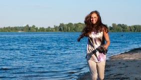 Jeune fille exécutant sur le fleuve Image stock
