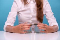 Jeune fille examinant la qualité de l'eau en verres Photo stock