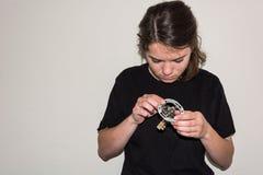 Jeune fille examinating une prise électrique endommagée Photographie stock