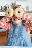 Jeune fille faisant des verres avec les beignets colorés photo stock