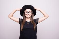 Jeune fille faisant l'émotion Habillé dans une chemise noire, chapeau noir, verres images libres de droits