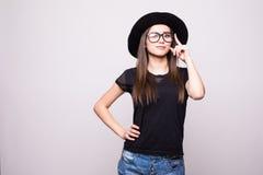 Jeune fille faisant l'émotion Habillé dans une chemise noire, chapeau noir, verres dans le studio Photos stock