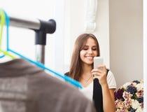 Jeune fille faisant la photo avec l'appareil-photo mobile dans la boutique Photographie stock