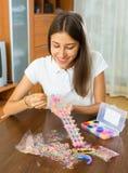 Jeune fille faisant le bracelet décoratif photographie stock