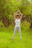 Jeune fille faisant le yoga sur une herbe verte Image libre de droits
