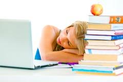 Jeune fille fatiguée dormant sur la table avec l'ordinateur portatif Photographie stock libre de droits