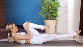 Jeune fille flexible aérobie appréciant formant le mensonge sur le tapis au plein tir de studio moderne de yoga banque de vidéos