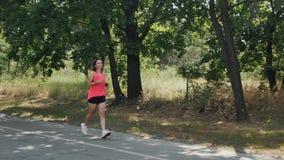 Jeune fille folâtre dans la chemise rose et les shorts noirs courts fonctionnant en parc Femme attirante dans des écouteurs avec  clips vidéos