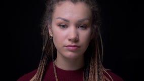 Jeune fille fraîche de brune avec des dreadlocks et perforation observant sur le plancher dans la confusion sur le fond noir banque de vidéos
