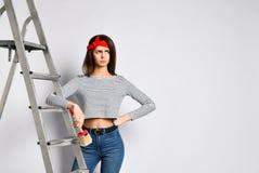 Jeune fille frustrée de brune avec une brosse et un escabeau - combien de travail devra être effectué sur peindre les murs photographie stock