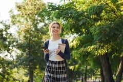 Jeune fille gaie d'école marchant dehors photos libres de droits