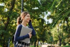 Jeune fille gaie d'école marchant dehors photo stock