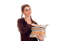 Jeune fille gaie d'étudiant avec des livres dans des vêtements bruns de sport regardant l'appareil-photo et le sourire d'isolemen Photos stock