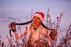 Jeune fille gaie dans un chapeau rouge sous les buissons Photo stock