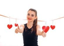 Jeune fille gaie de brune posant avec le coeur rouge d'isolement sur le fond blanc Concept de jour de valentines de saint Amour Images libres de droits