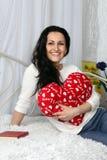 Jeune fille gaie et jolie s'asseyant sur le lit, elle tient un oreiller en forme de coeur studio Image libre de droits