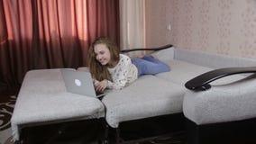 Jeune fille gaie et mignonne à l'aide de l'ordinateur portable d'intérieur clips vidéos