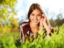 Jeune fille gaie se trouvant sur l'herbe verte photographie stock