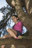 Jeune fille haute dans un vieil arbre rêvassant Images libres de droits