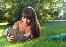 Jeune fille heureuse à l'aide d'un ordinateur de tablette Photos stock