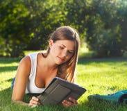 Jeune fille heureuse à l'aide d'un ordinateur de tablette Image libre de droits