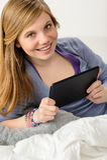 Jeune fille heureuse à l'aide du comprimé numérique Photographie stock libre de droits