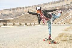 Jeune fille heureuse élégante dans un chapeau et des combinaisons de denim équilibrant au milieu d'une route de montagne sur un l Images stock