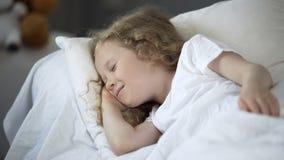 Jeune fille heureuse appr?ciant de bons r?ves dans le lit chaud, enfant souriant tandis qu'endormi image stock