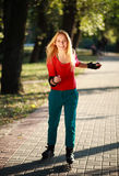 Jeune fille heureuse appréciant le patinage de rouleau en parc Images stock
